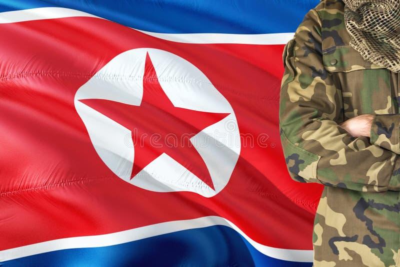 Korsad nordkoreansk soldat för armar med den nationella vinkande flaggan på bakgrund - Nordkorea militärt tema fotografering för bildbyråer