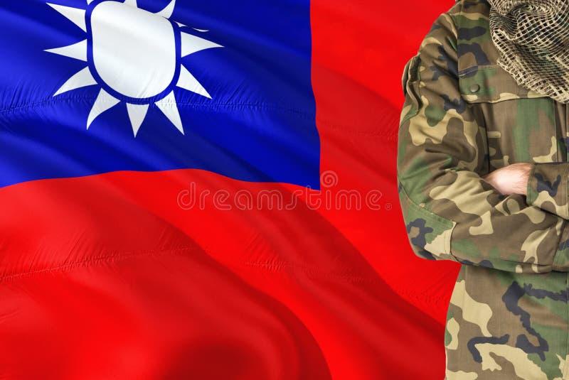 Korsad taiwanesisk soldat för armar med den nationella vinkande flaggan på bakgrund - Taiwan militärt tema royaltyfria bilder