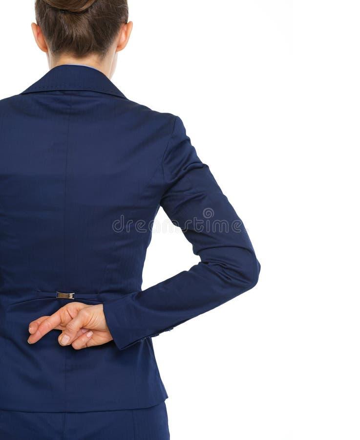 Korsade fingrar för affärskvinna innehav bak baksida. bakre sikt royaltyfria bilder