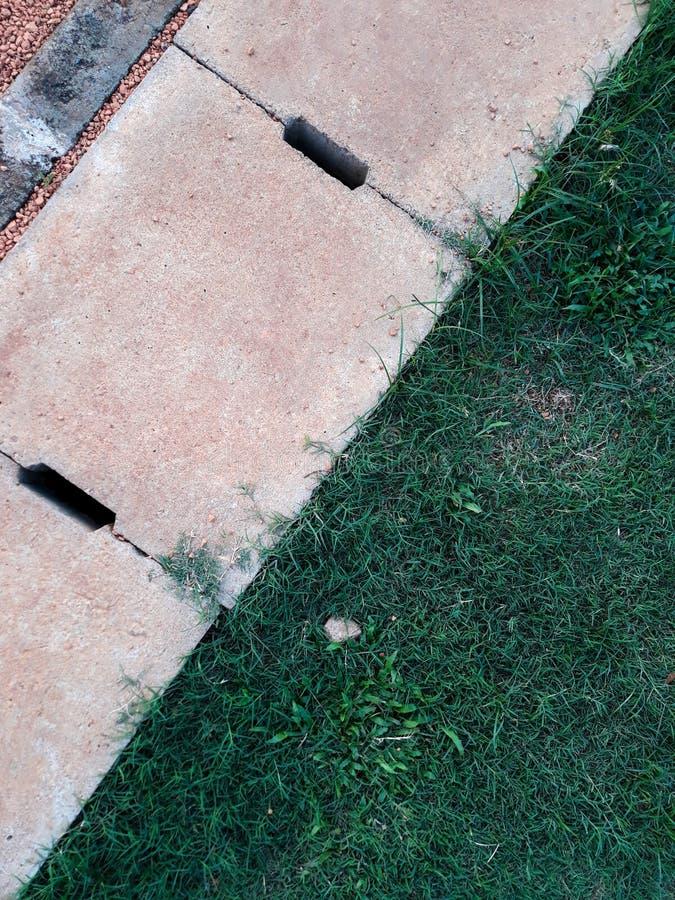 Korsat och grönt gräs för cementavrinningspisgaller med abstrakt bakgrund fotografering för bildbyråer