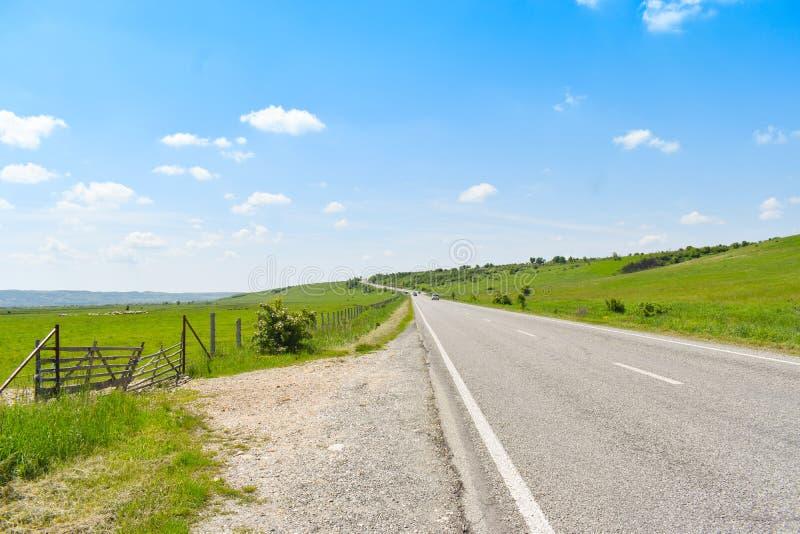 Korsning för lång väg för asfalt den gröna dalen i en solig sommardag med ljus blå himmel arkivbilder