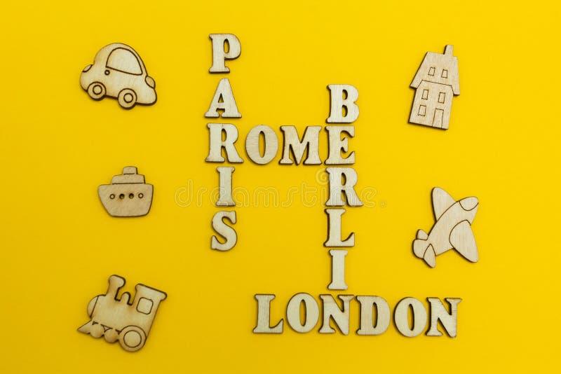 Korsord av namnen av städerna: 'Paris, London, Berlin, Rome 'på en gul bakgrund Trädiagram av ett flygplan, en tra royaltyfria bilder