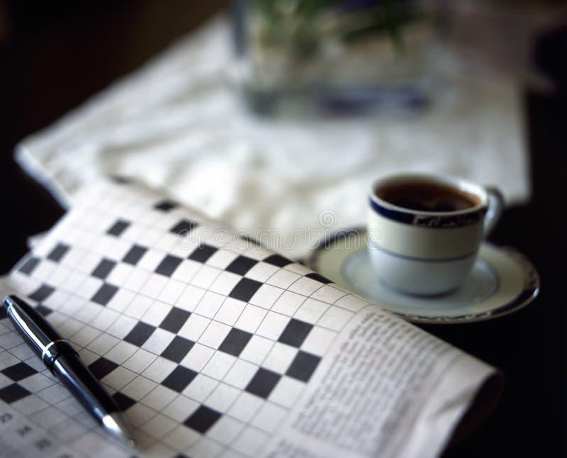 Korsordpussel med pennan och svartcoffe arkivfoton