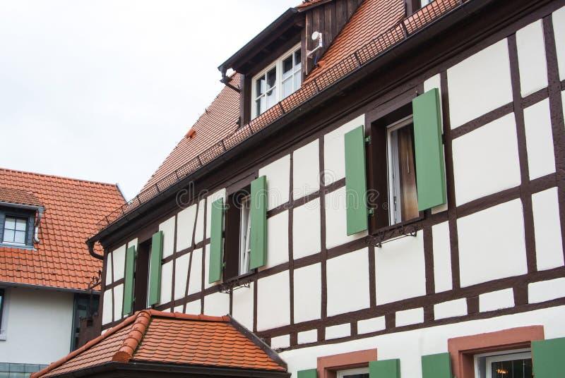 Korsvirkes- hus för traditionell tysk by med trägarnering och gröna slutare av fönstren royaltyfri fotografi