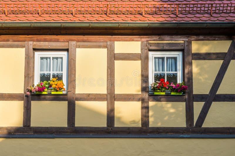 Korsvirkes- hus med fönstret och färgrika blommor royaltyfria bilder