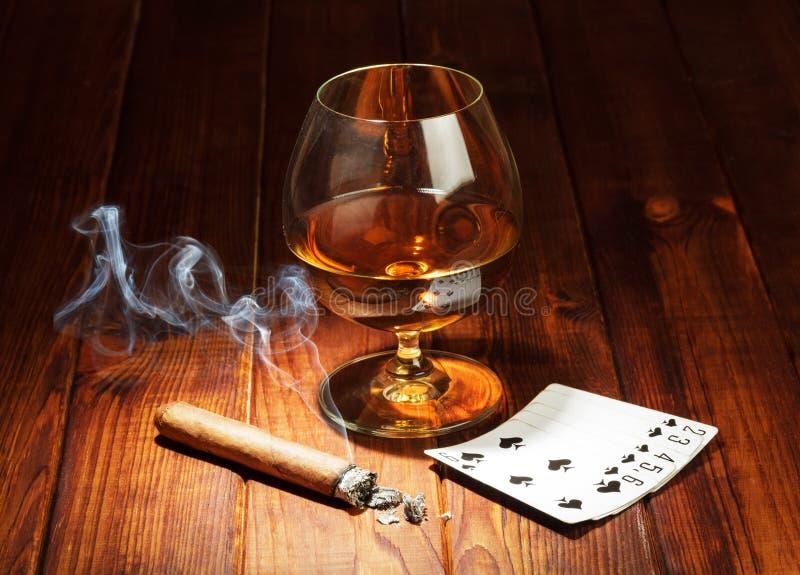 Kort, cigarr och exponeringsglas av whisky royaltyfri fotografi