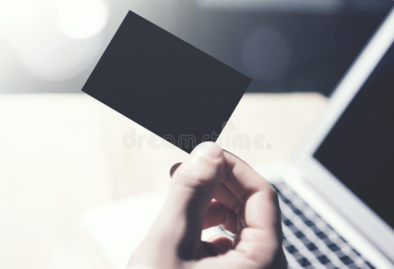 Kort för affär för svart för mellanrum för visning för Closeupbildman och använda den moderna bärbara datorn på suddig bakgrund f arkivbilder