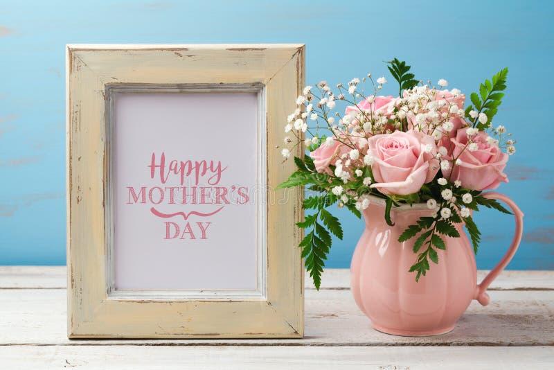 Kort för hälsning för moderdag med buketten för rosa färgrosblomma och fotoramen royaltyfria bilder