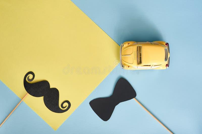 Kort för hälsning för faderdag med den gula leksakbilen och den svarta pappers- mustaschen och band på blå bakgrund med stället f arkivbilder