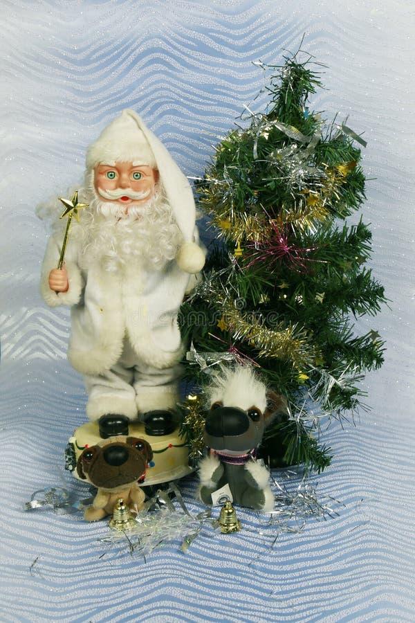Kort för hälsning för foto för ` s för nytt år med Santa Claus och gullig hundkapplöpning på bakgrunden av den dekorerade julgran royaltyfri bild