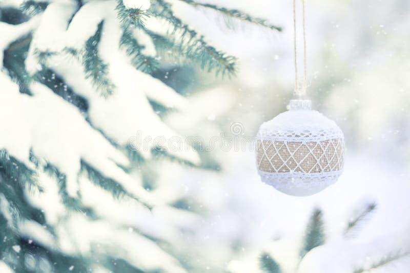 Kort för hälsning för julvinterferie Vit lantlig julprydnadboll med säckväv på gröna julträd med snö royaltyfri fotografi