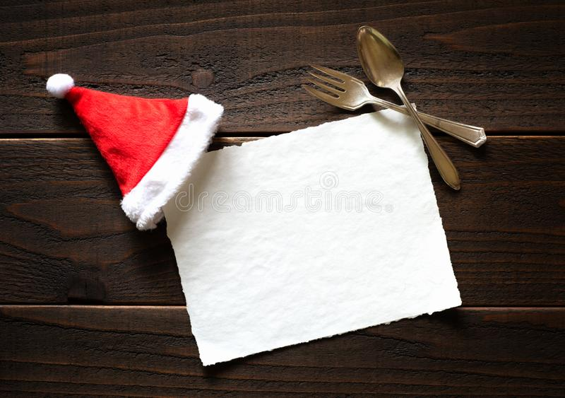 Kort för julferiepapper med den röda och vita Santa Claus Hat och gaffeln och sked på mörk lantlig trätabellbakgrund arkivfoton