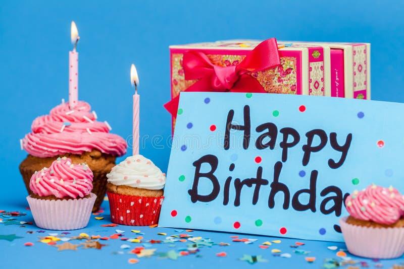 Kort för lycklig födelsedag med gåva och muffin arkivbilder