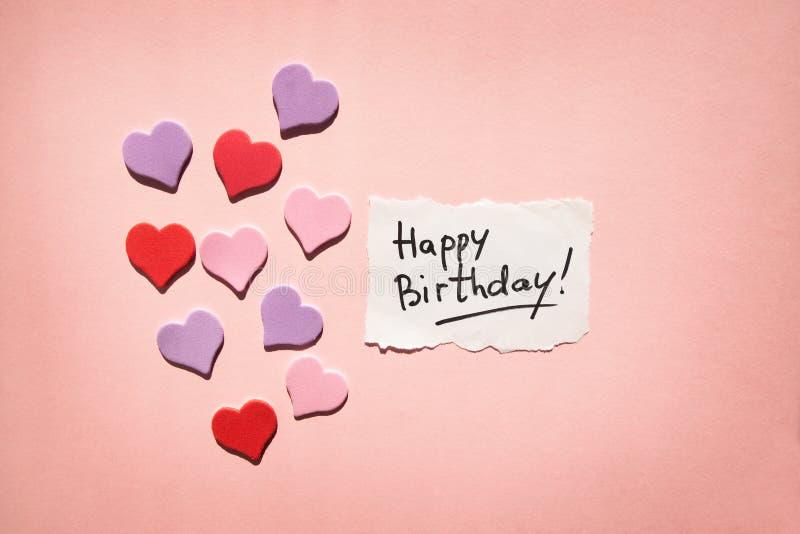 Kort för lycklig födelsedag med text och hjärtor på härlig rosa bakgrund arkivfoto