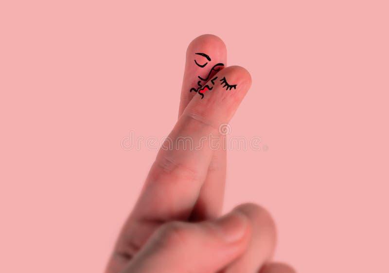 Kort för valentindaghälsning som presenterar handen med två fingrar som målas tillsammans som man- och kvinnaframsidan som kysser royaltyfria foton