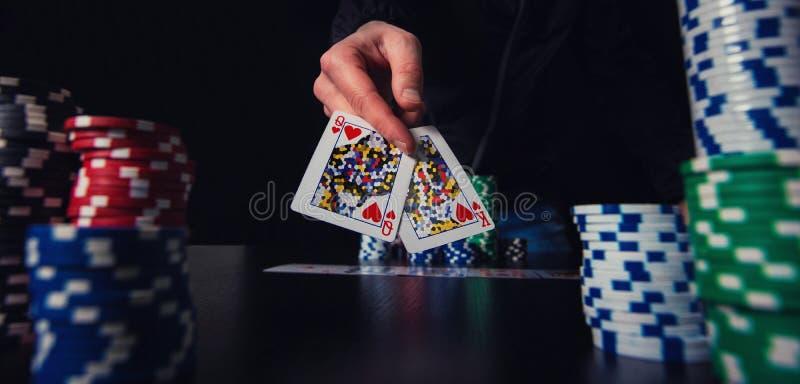 Kort för visning för hand för pokerspelare som spela slå vad chiper på kasinotabellen royaltyfri fotografi