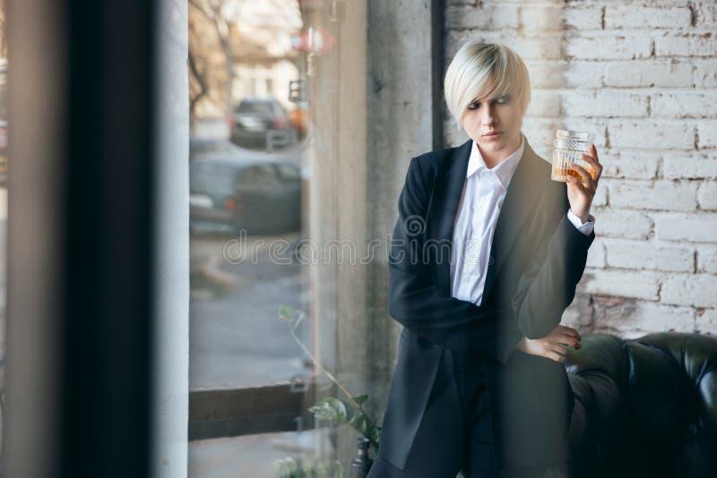 Kort haired blond flicka med ett exponeringsglas av whisky arkivbild