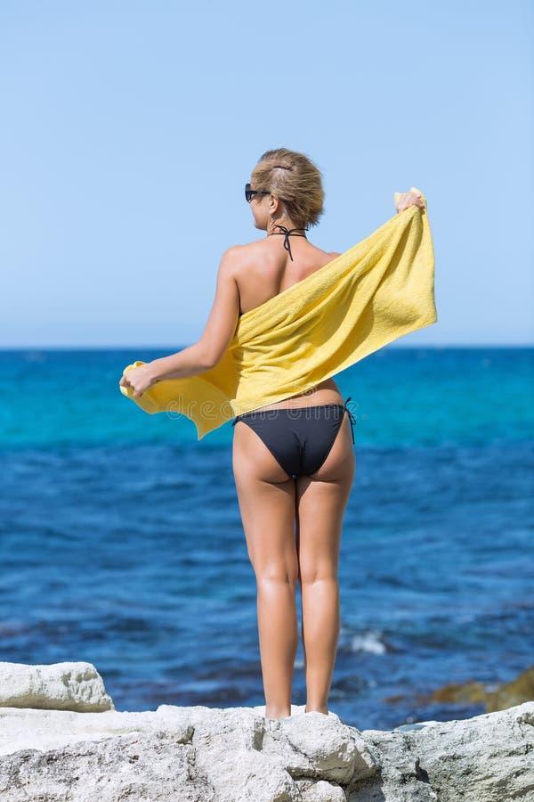 Kort-haired blond kvinna som vilar på den steniga kusten arkivfoton