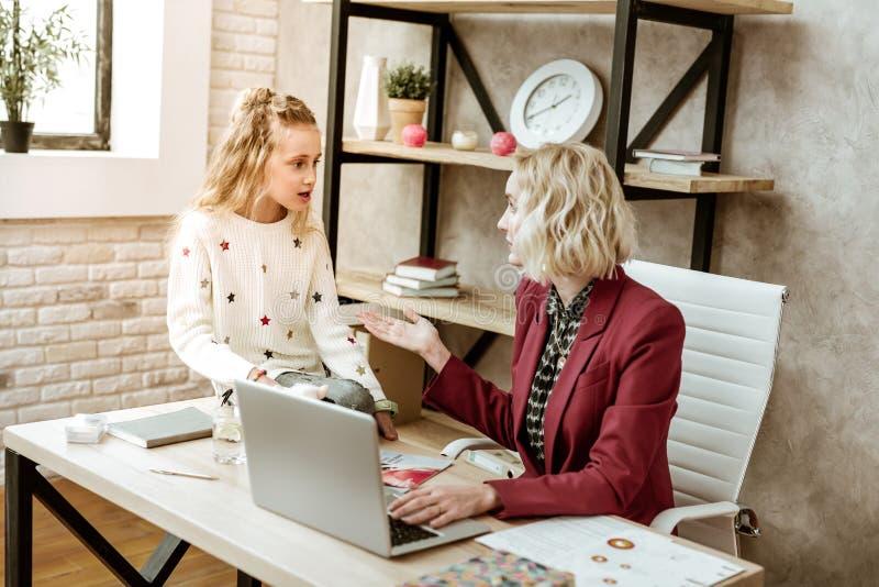 Kort-haired ilsken blond kvinna som har viktig konversation med dottern arkivbild