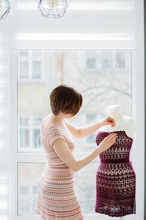 Kort-haired kvinnlig bekläda formgivare som använder klänningattrappen på den hemtrevliga hemmiljön, frilans- livsstil Skjuten lo royaltyfria foton