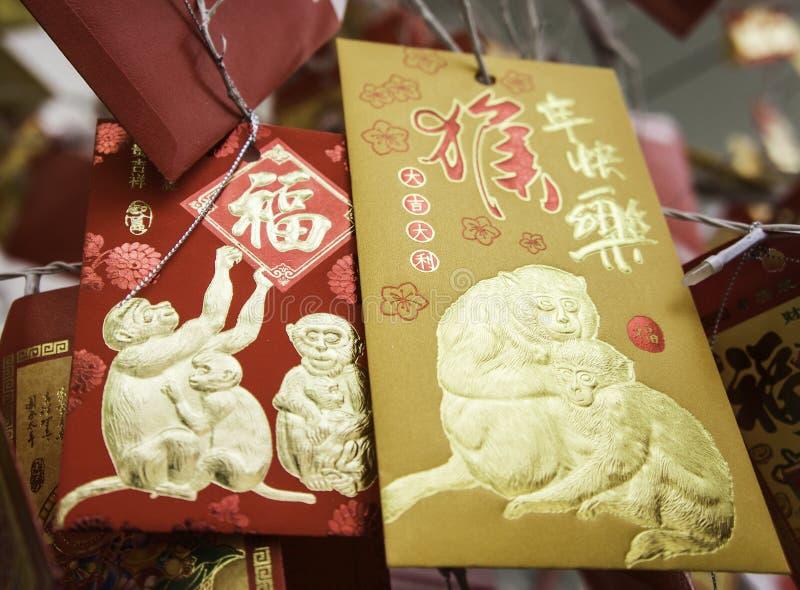 Kort med bilden av en apa som hänger på en julgran TET som snart kommer kinesiskt nytt år arkivfoto