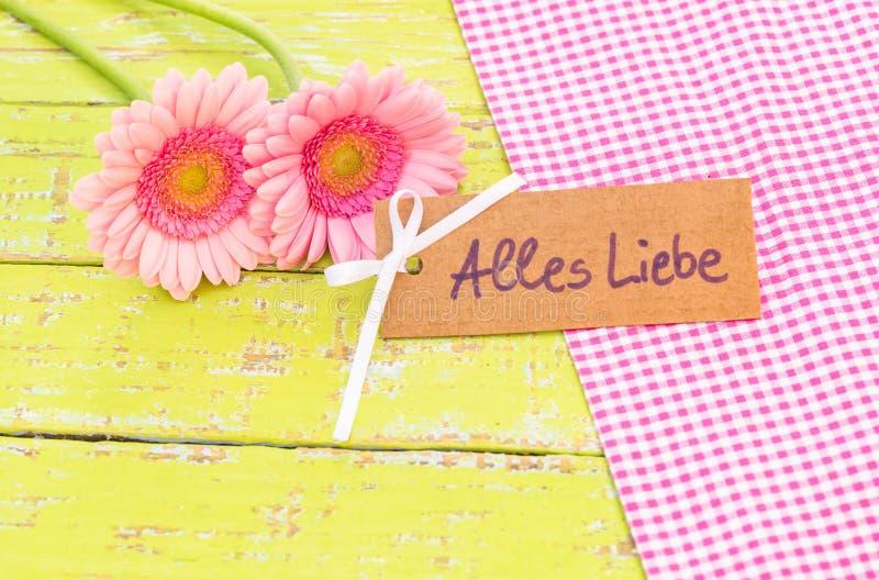 Kort med gratulationer - tysk text, Alles Liebe, hjälpmedel älskar, och rosa färgen blommar garnering arkivfoto
