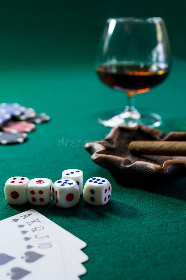 Kort, tärningen, chiper, ett exponeringsglas av konjak och cigarren på en grön biljardduk, leken är arkivfoto