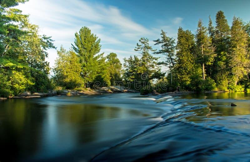 Kort vattenfall som ut slätas av lång exponering arkivbilder