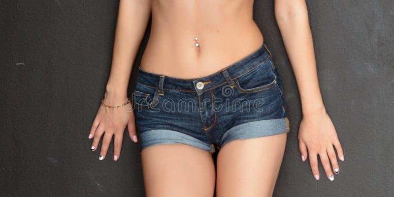 Korte blauwe Jean-borrels op het lichaam van een jong gelooid meisje op grijze achtergrond stock foto's
