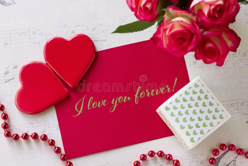 Kortet för valentindaghälsningen med hjärtor för rosgåvaasken och bokstäver älskar jag dig för evigt arkivbild