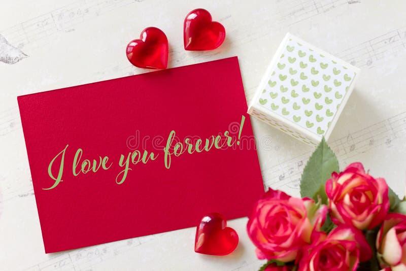 Kortet för valentindaghälsningen med hjärtor för rosgåvaasken och bokstäver älskar jag dig för evigt arkivfoton