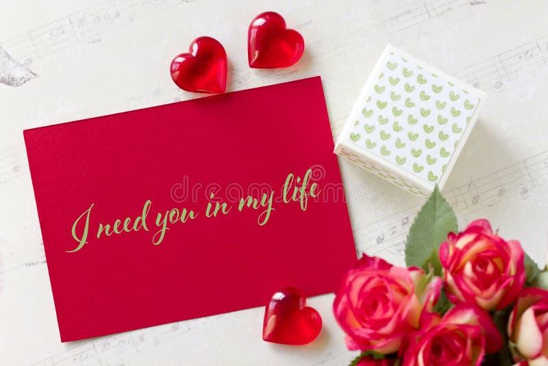 Kortet för valentindaghälsningen med hjärtor för rosgåvaasken och bokstäver behöver jag dig i mitt liv royaltyfri fotografi
