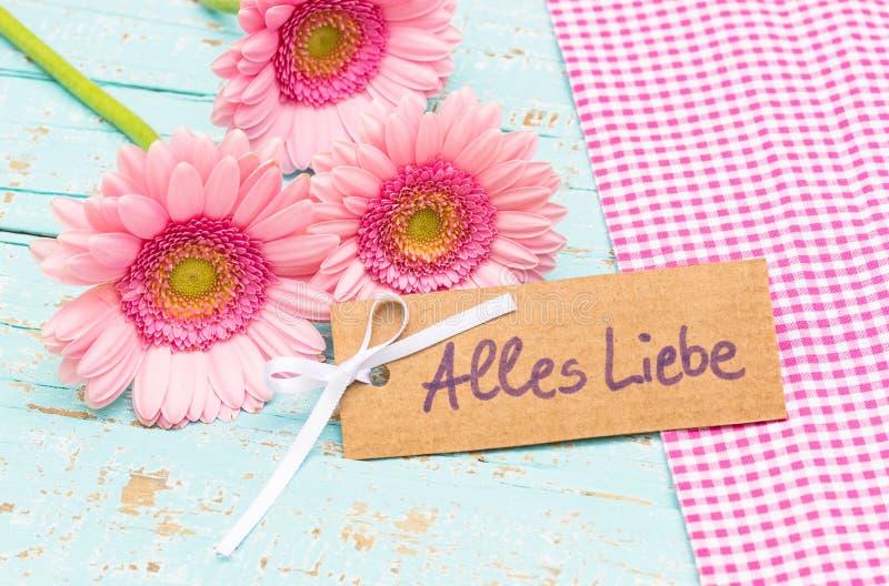 Kortet med tysk text, Alles Liebe, hjälpmedel älskar, och rosa färgen blommar för valentin- eller moderdag fotografering för bildbyråer