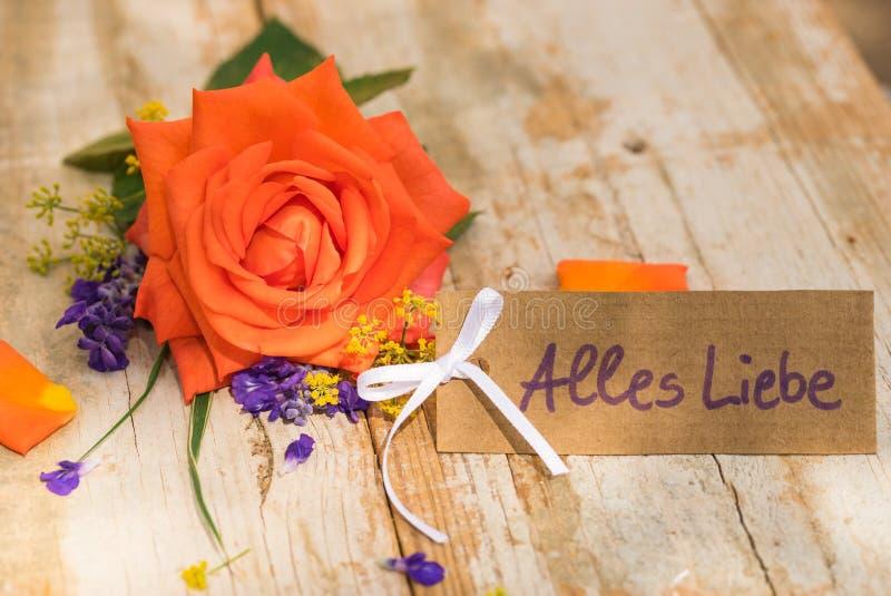 Kortet med tysk text, Alles Liebe, hjälpmedelförälskelse med den färgade apelsinen steg royaltyfria foton