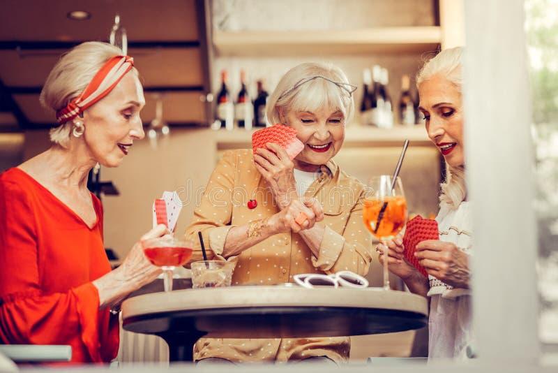 Kortharige glimlachende vrouw die haar kaart van vrienden verbergen royalty-vrije stock foto