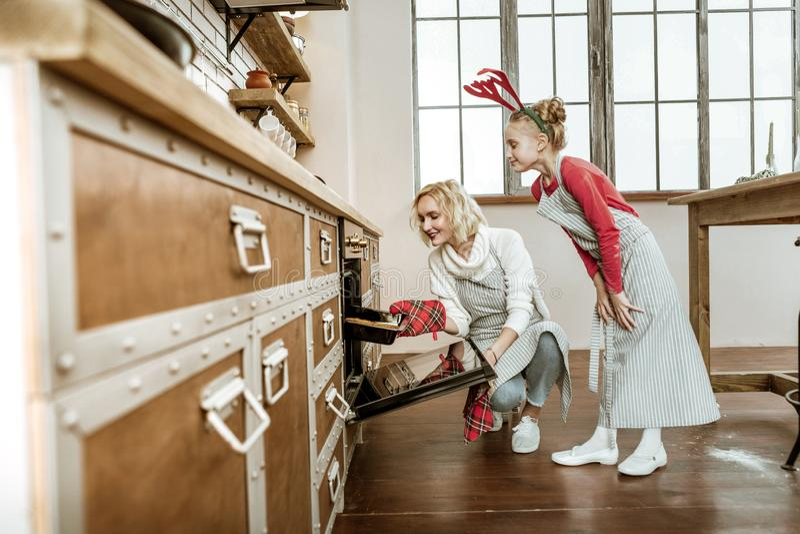 Kortharige richtende vrouw die speciale handschoen voor het zetten van hete pan gebruiken royalty-vrije stock fotografie