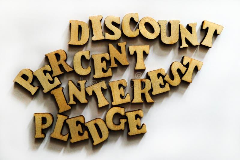 Korting, rente, percenten en belofte Woorden van houten brieven stock fotografie