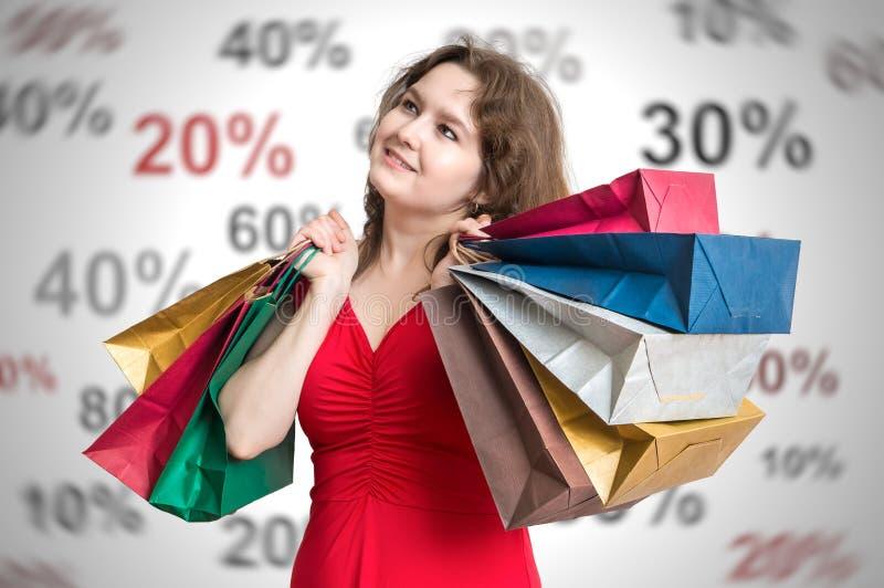 Kortingen en het winkelen concept De jonge en gelukkige vrouw houdt vele kleurrijke het winkelen zakken in handen royalty-vrije stock fotografie