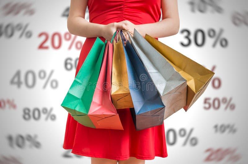 Kortingen en het winkelen concept De jonge vrouw houdt vele kleurrijke het winkelen zakken in handen stock foto's
