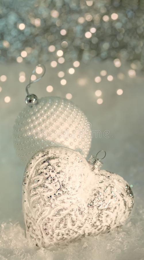kortjul som greeting Exponeringsglashjärta och en vit boll med pärlor på en snö Suddig grå bakgrund av gul bokeh och ljus royaltyfri bild