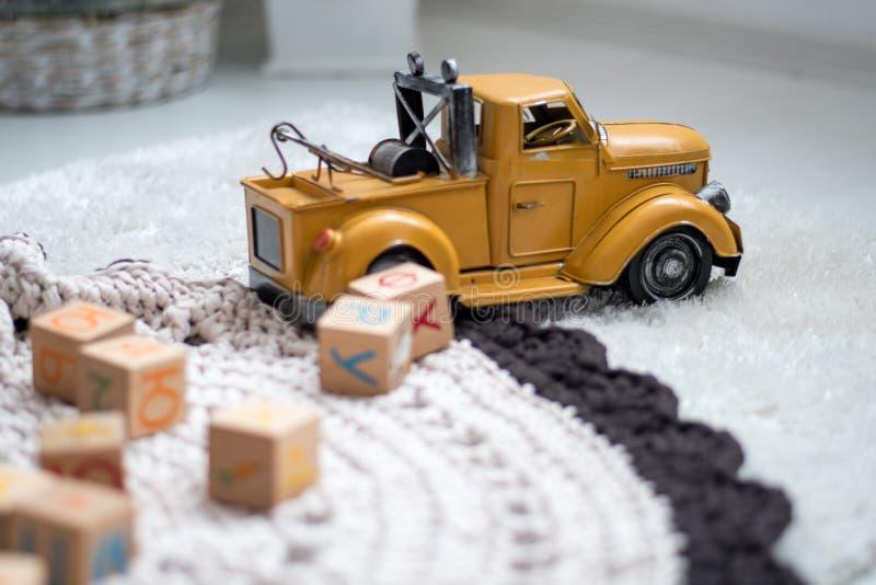 Kortkortguling ruck leksaken på en matta som omges av kuber royaltyfria foton