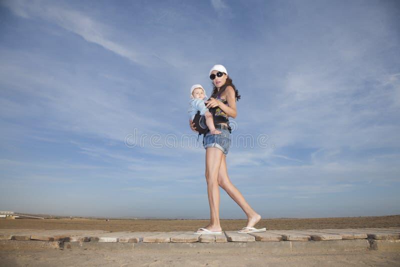 Kortsluter mamman med behandla som ett barn i ryggsäck arkivbild