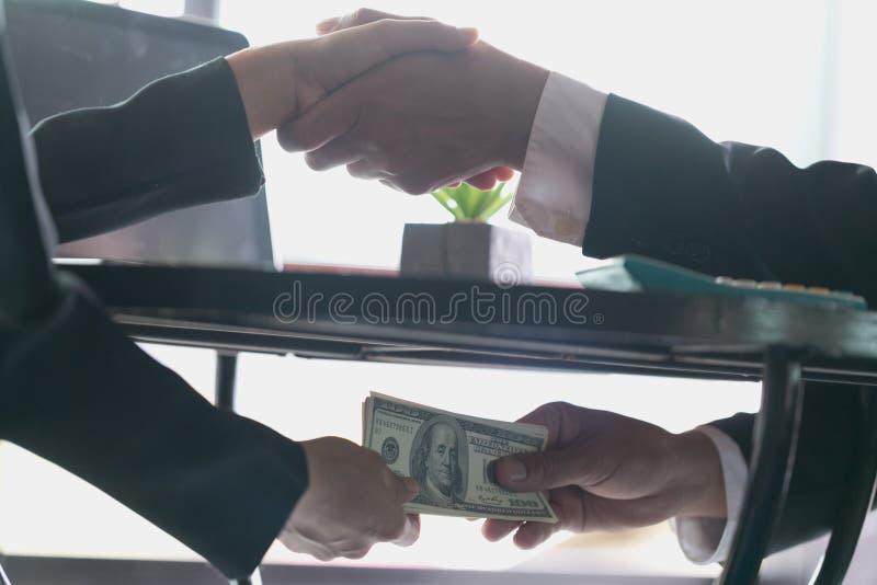 Korumpujący biznesmen pieczętuje transakcję z dostawaniem i uściskiem dłoni łapówka pieniądze, anty łapówkarstwo i korupcji pojęc fotografia royalty free