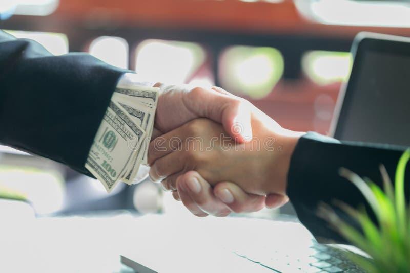 Korumpujący biznesmen pieczętuje transakcję z dostawaniem i uściskiem dłoni łapówka pieniądze, anty łapówkarstwo i korupcji pojęc obrazy stock