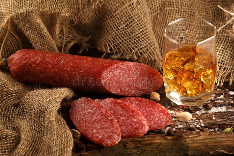 Korv i ett exponeringsglas av whisky royaltyfri bild