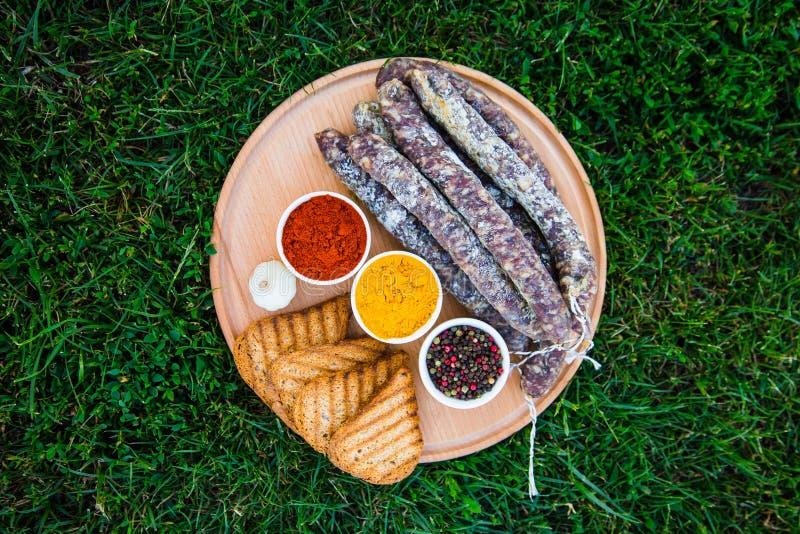 Korv, krutonger och kryddor på ett träbräde Gräs i bacen royaltyfri bild