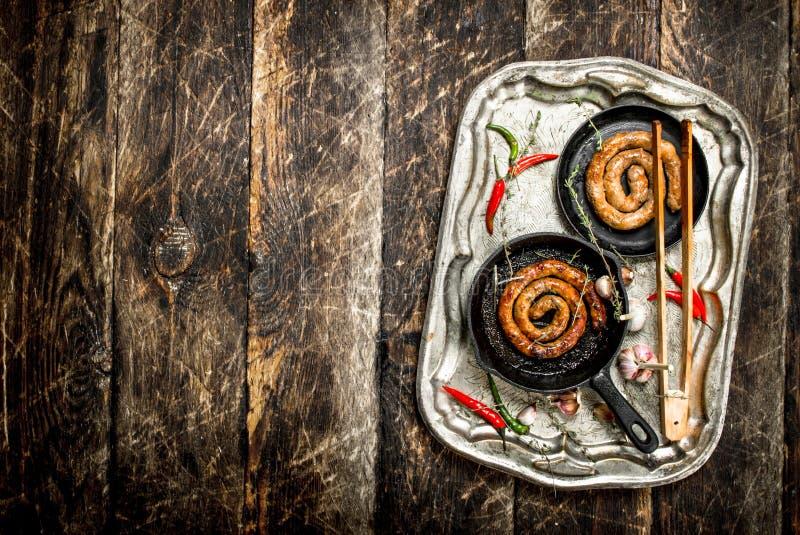 Korvar i pannor på ett stålmagasin med peppar för varm chili arkivfoto