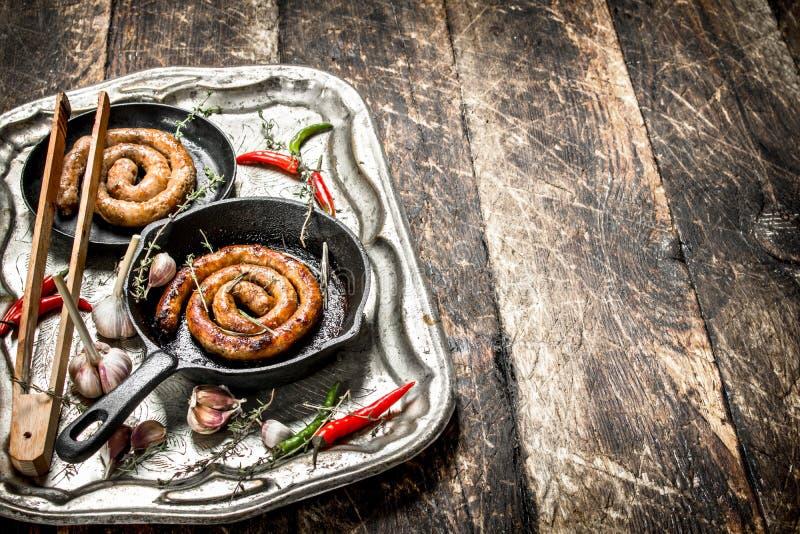 Korvar i pannor på ett stålmagasin med peppar för varm chili arkivbilder