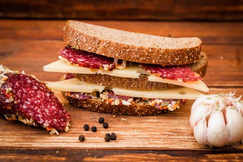 Korven lagade mat den rökte korven, ost med mörker för frukosten, smörgåsen, svart bröd, vitlök, svartpeppar, lagerblad på tabell royaltyfria bilder