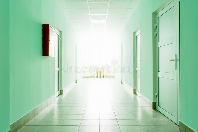 Korytarz z jaskrawym światłem od okno, sala z zieleni ścianami i biali drzwi, zdjęcie royalty free